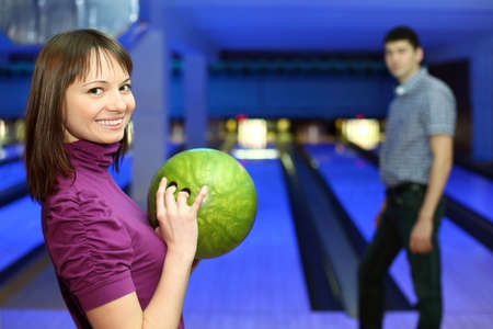 exactness: Girl holds ball for bowling and smiles, and man look at it, focus on girl Stock Photo