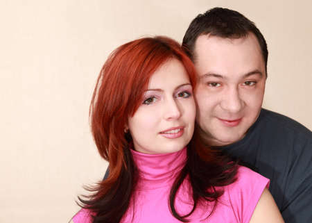 young wife: husband and her young wife in pink shirt in house; focus on woman
