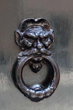 big beautiful metal doorknob, holding human head in his mouth stick photo