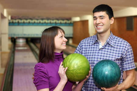 Young man and girl hold balls for bowling and laugh merrily photo