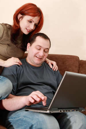 young wife: young wife and husband sit on brown sofa and looking at laptop screen, focus on man