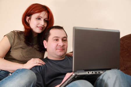 young wife and husband sit on brown sofa and looking at laptop screen, focus on man, horizontally framed shot Stock Photo - 17730349
