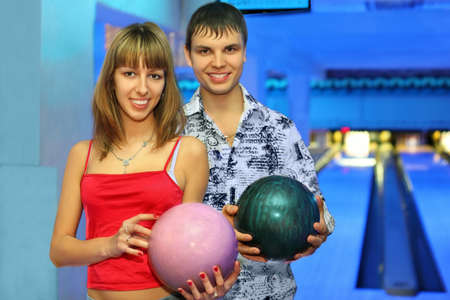 Fellow and girl stand alongside with balls for bowling during rest in club, focus on girl photo