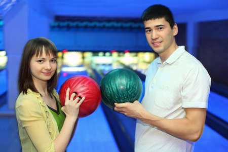 Girl and youth turned  to each other and adjoin balls for bowling photo