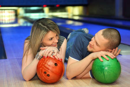 Fellow and girl lie on parquet and look on each other leaning against balls for bowling, focus on girl photo