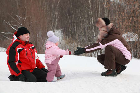 little daughter goes from father to mother at snow in winter, focus on girl photo