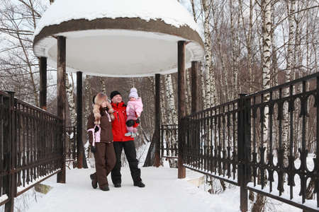 capote: father, mother and little daughter standing in rotunda, snow, winter