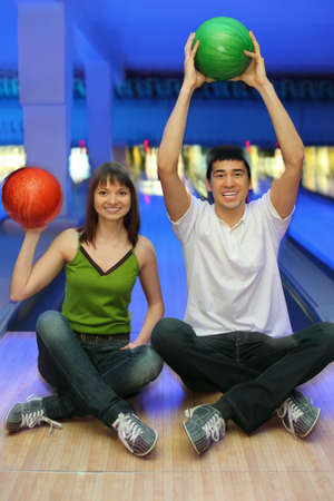 Fellow and girl sit on parquet and lift upwards balls for bowling photo
