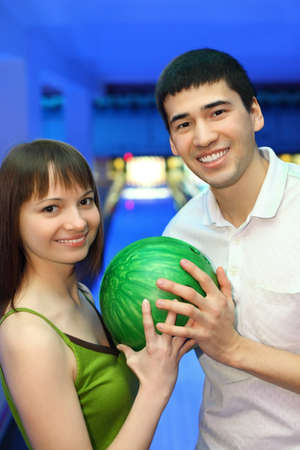 Fellow and girl turned to each other and hold one ball for bowling, focus on man photo