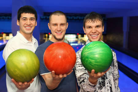 Friends stand alongside and ahead in hands hold balls for bowling photo