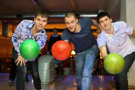 exactness: Three fellows throw balls on lane in bowling club Stock Photo