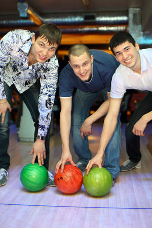 Three men bent over to heave up balls for bowling, focus on fellow in center photo