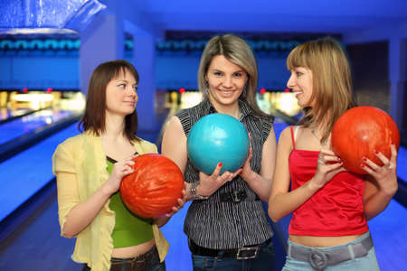 exactness: Three girlfriends hold balls for bowling and look on each other, focus on  girl in center Stock Photo