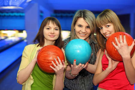 closely: Girls closely stand alongside, hold balls for bowling and smile