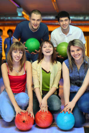 Three girlfriends squatting and behind stands two fellows  and everybody holds ball for bowling, focus on girls photo