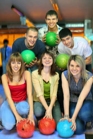 Three girls of squatting and three fellows  back stand with balls in bowling club, focus on girl in center photo