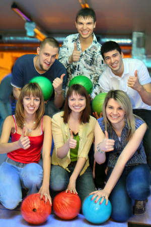 Three girls of squatting and three men behind with balls for bowling of  hands shows of ok, focus on girls photo