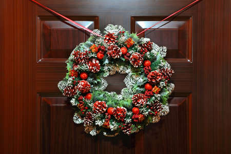 hangs: Large artificial circled wreath with knops and bead hangs during Christmas on door Stock Photo
