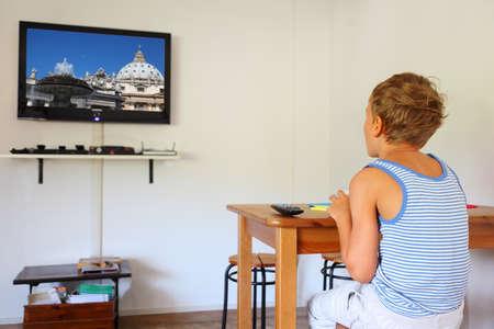 テーブルに座ってテレビを見て、テレビで Pavel Losevsky によって写真のストライプのシャツ地のリトルボーイ 写真素材