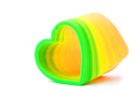 Plastic toy spring in heart-shaped, yellow and green colours photo