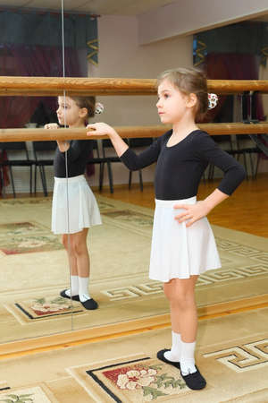 little girl wear pointe in ballet class near frame and large mirror