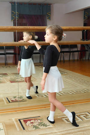 stockings feet: little girl wear pointe trains in ballet class near frame and large mirror Stock Photo