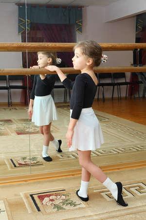 pantimedias: niña de desgaste de punta los trenes en clase de ballet cerca de marco y espejo grande Foto de archivo