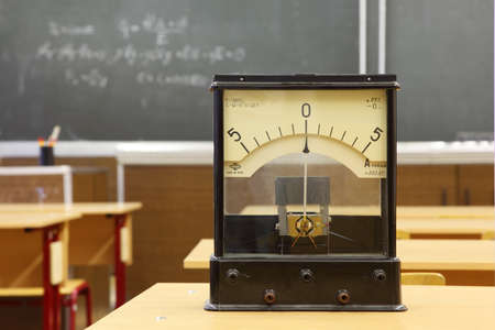 Educational galvanometer with not real number 555 on yellow desk in empty physics school class; formula on blackboard photo