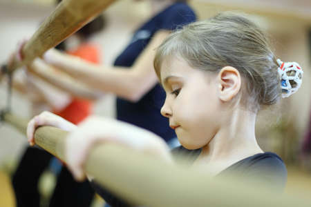 concentrated face of little girl in ballet class near frame and large mirror photo