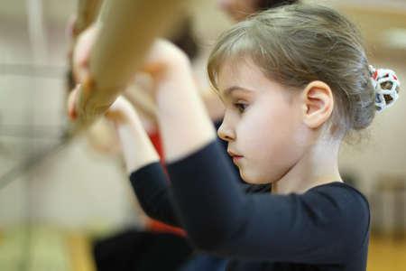 小さな女の子がフレームと大きな鏡の近くにバレエ クラスの深刻な顔