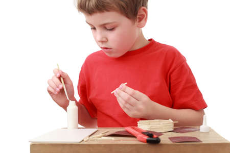 boxcutter: little boy in red T-shirt crafts at small table, boxcutter, glue Stock Photo