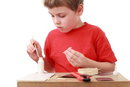 pegamento: niño pequeño en rojo camiseta de artesanía en pequeña mesa, cúter, pegamento