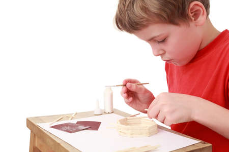 captivate: little boy in red T-shirt crafts at small table, glue, side view