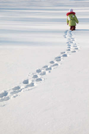 little girl in green jacket walking on snow, footprints in snow, behind Stock Photo