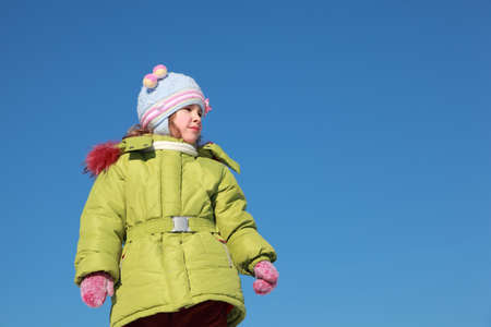 little girl in green jacket at winter, blue sky, warm clothing Stock Photo - 17720858