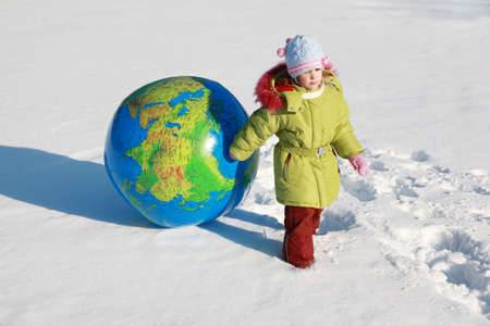 beautiful little pensive girl drags big inflatable globe on outdoors in winter photo