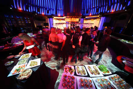 night club interior: crowd of people relaxing in bar of night club, drinking and dancing, smorgasbord