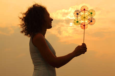 beautiful young woman holding toy whirligig and smiling at sunset photo