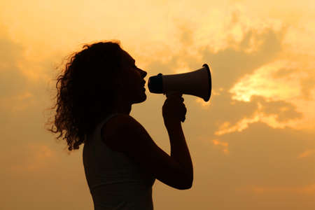 beautiful woman holding megaphone and shouted into it at sunset 스톡 콘텐츠