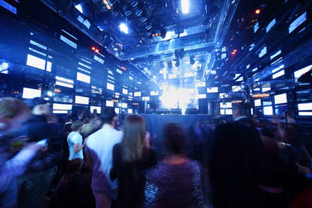 People dancing at concert in nightclub, light show and loud music  Editoriali