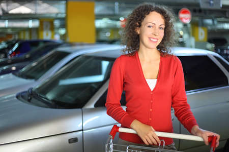 beautiful young woman in red cardigan with cart standing in underground car park and smiling Stock Photo - 17719274