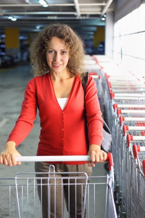 beautiful young woman with cart standing in indoor car park, row of shop carts Stock Photo - 17719275