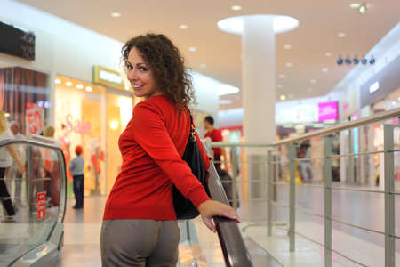 beautiful young woman standing on escalator into large store photo