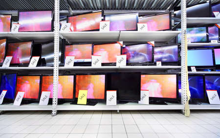 Plasma TVs with big diagonal stand on shelves in large store; wide range