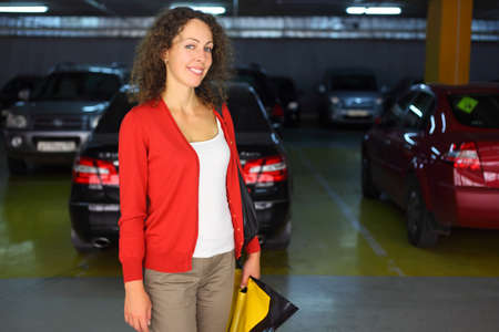 beautiful young woman in red cardigan with parcels standing in underground car park and smiling Stock Photo - 17719273