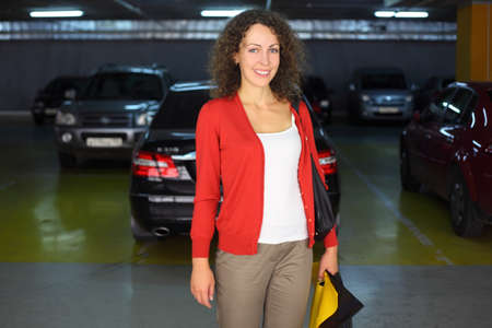 beautiful young woman with parcels standing in underground car park and smiling Stock Photo - 17719317
