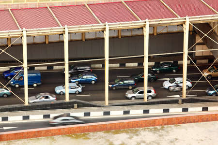 many cars fast go on road under red roof at day, fast motion photo