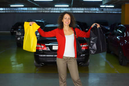 beautiful happy woman with purchases standing in underground car park and smiling Stock Photo - 17719272
