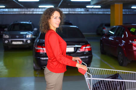 beautiful young woman with cart standing in underground car park of big shop and smiling Stock Photo - 17719318