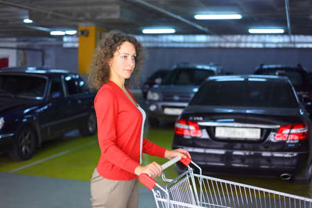 red cardigan: beautiful young woman in red cardigan with cart standing in underground car park Stock Photo